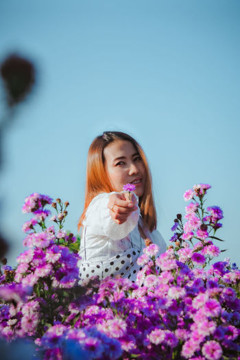 Beautiful young woman with purple flowers against plants