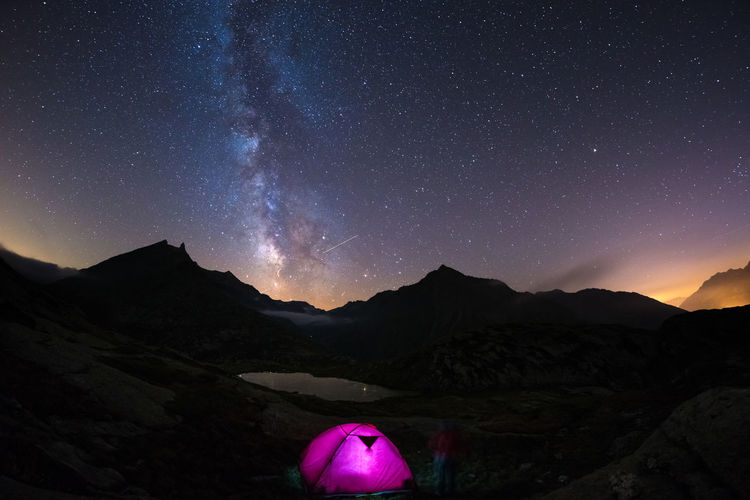 View of illuminated tent on mountain against sky at night