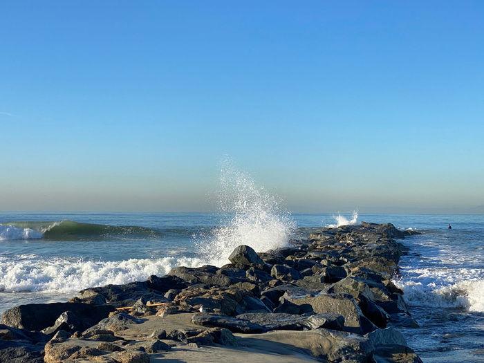 Sea waves splashing on rocks against clear sky