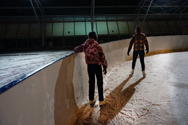 Rear view of people ice-skating at night