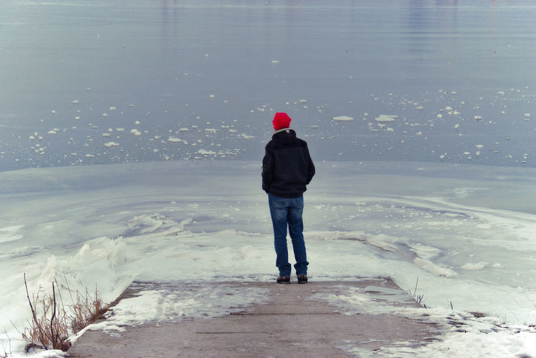 Red Hat Winter Cold Temperature Cracked Ice Frozen River Full Length Lifestyles Man In Nature Men Nature One Man Only One Person Outdoors Real People Rear View River Bank  Snow Standing Warm Clothing Winter