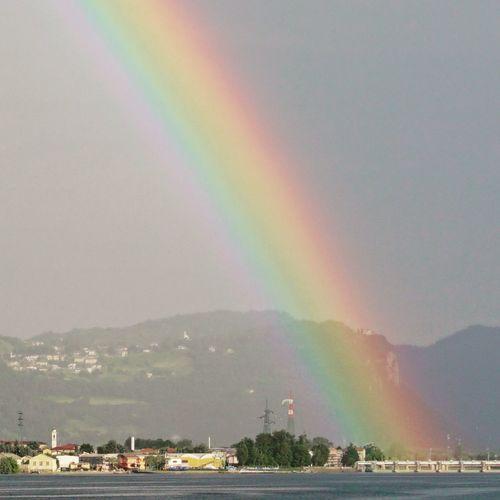 Rainbow over city by sea against sky