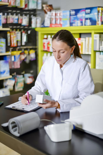 Female pharmacist writing while sitting at table against shelf in store