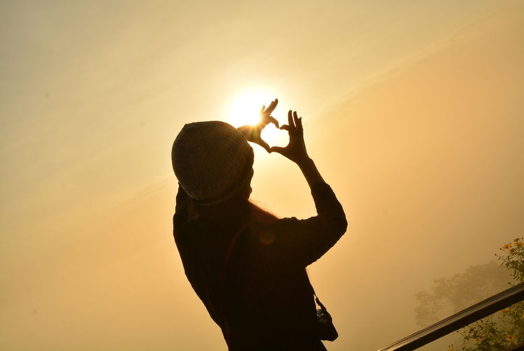 Silhouette woman making heart shape while standing against sky during sunset