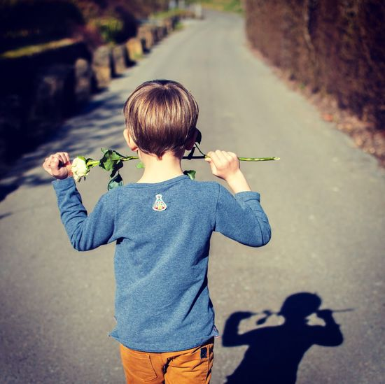 Rear view of boy standing on road