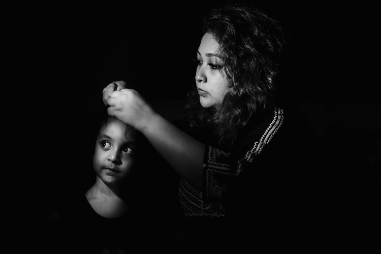 Mother and daughter against black background