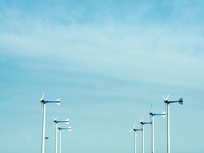 Low angle view of windmills against blue sky