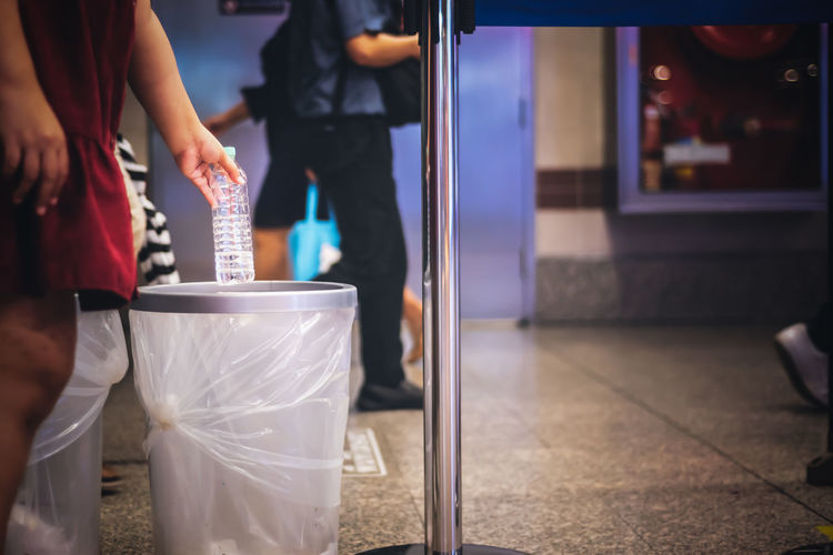 Midsection of woman holding bottle over dustbin on floor