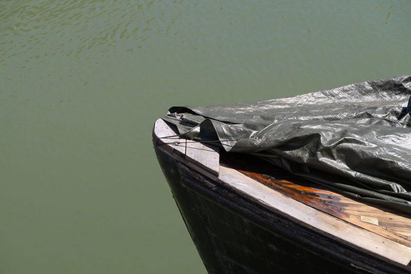 Cropped image of wooden boat covered with tarpaulin at lake