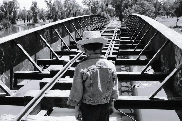 Rear View Of Boy Standing On Railway Bridge During Sunny Day