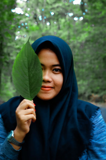 Portrait of smiling woman wearing hijab holding leaf