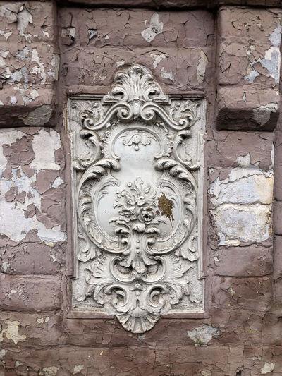 Close-up of ornate door on brick wall
