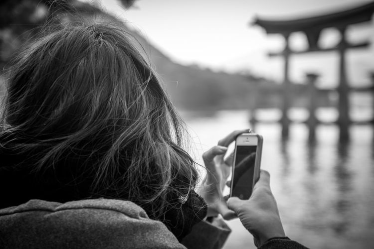 Rear view of woman using mobile phone at lake