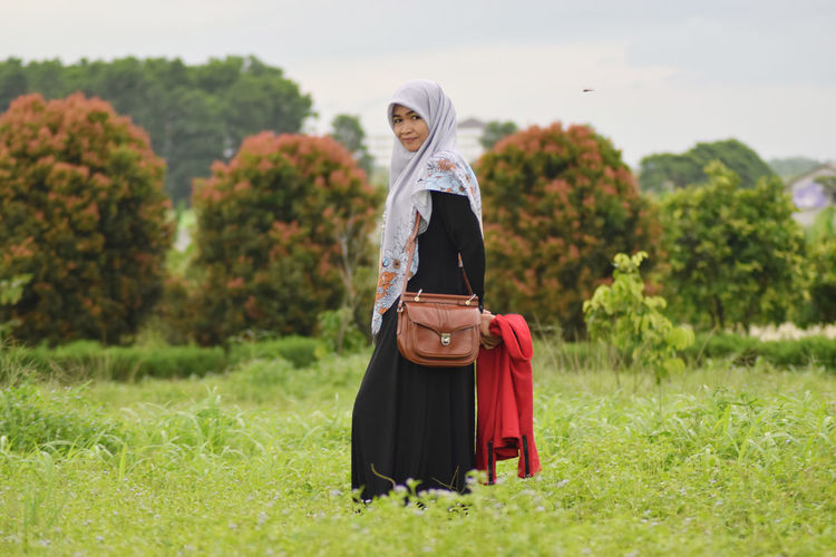 Portrait of smiling woman in hijab standing on field