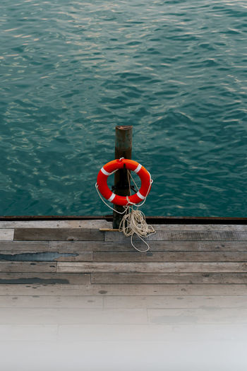 high angle view of a Lifebelt hanging on a wooden post at the railing Water Day Nature Outdoors High Angle View Safety Wood - Material Pier Rope Lifebelt Security Turquoise Colored Sea Ocean Pier Tourism Marine Railing Protection Red Life Belt Tied Up Post Wooden Wooden Post Cruise