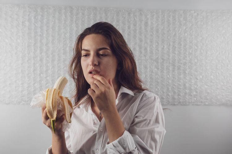 Woman Eating Banana At Home