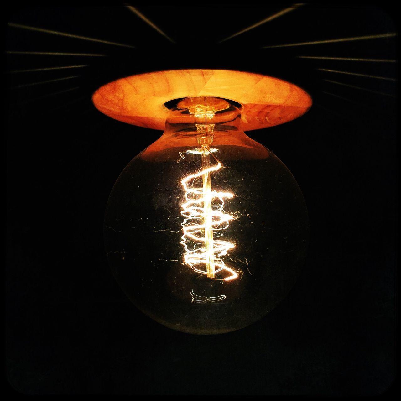 Close-Up Of Lit Light Bulb Over Black Background