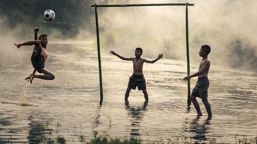 Shirtless boys playing soccer in lake