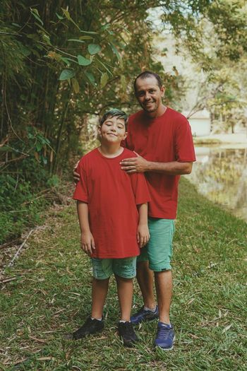Portrait of smiling boy standing with father against plants at park