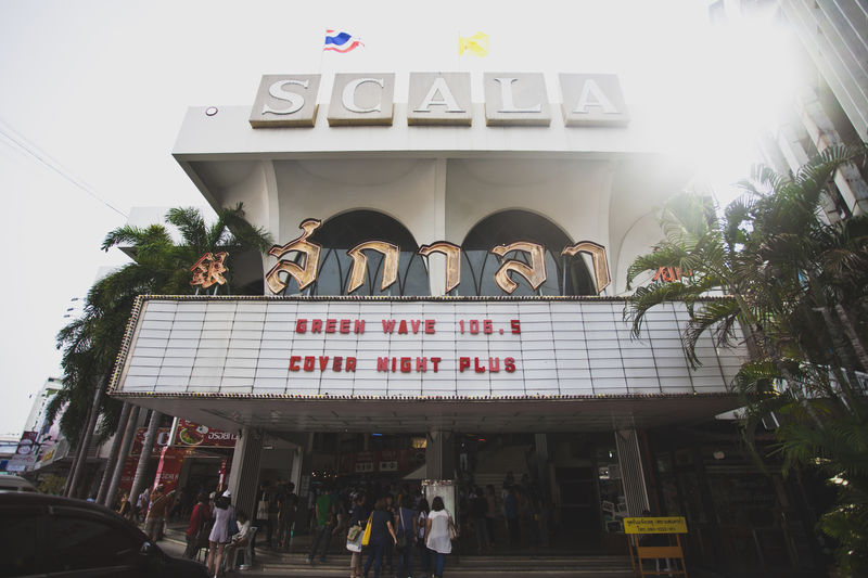 the old Scala theater in Bangkok Architecture Building Exterior City City Life Day Entrance Non-western Script Old Buildings Outdoors Person Scala Sky Sun Flare Symbol Text Thai Thailand Theater Theatre