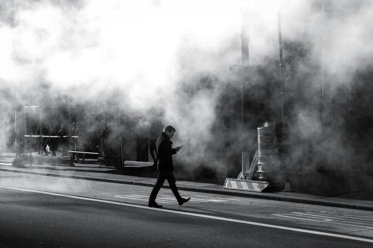 Full length of man smoking on road