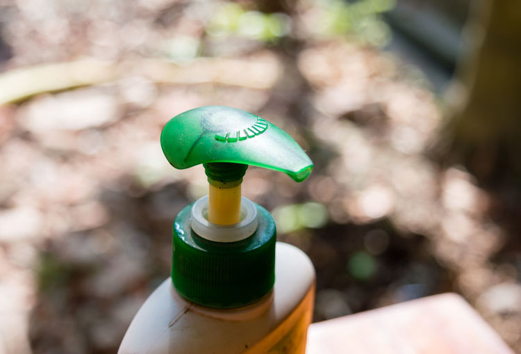 Close-up of green holding bottle against blurred background