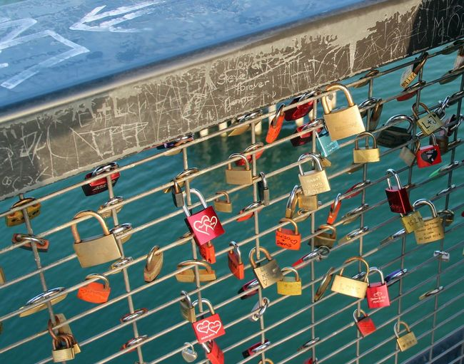 Padlocks Attached On Bridge Railing Over River