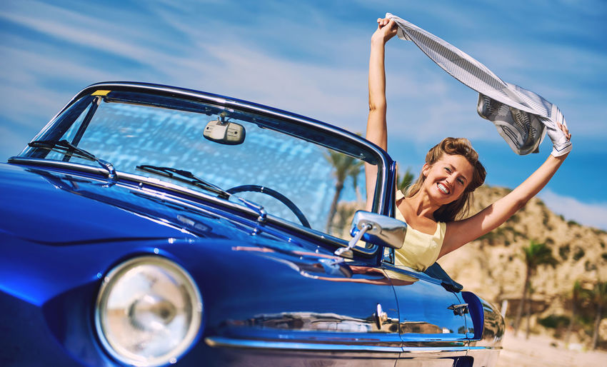 Smiling woman holding scarf aloft while sitting in car