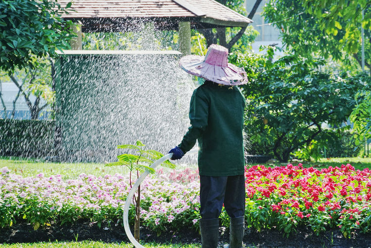 Man watering flowers in garden