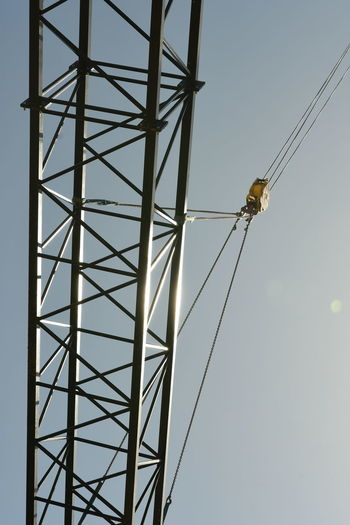Low angel view of girder hanging by crane against sky