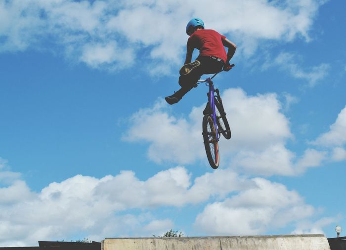 Low angle view of man jumping with bicycle against sky