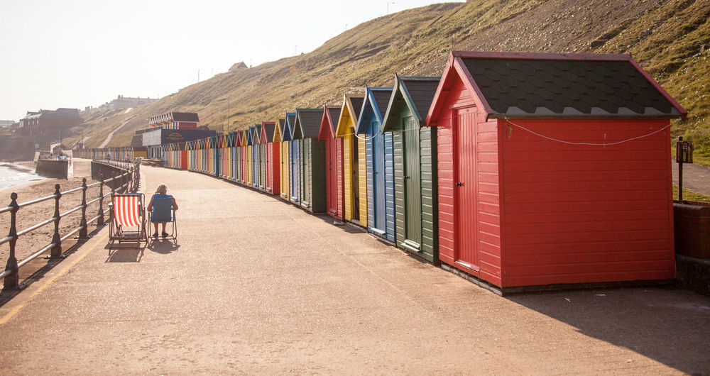 Adult Architecture Beach Beach Huts Building Exterior Built Structure Day In A Row Multi Colored One Man Only One Person Only Men Outdoors People Sand Sky Sunlight The Way Forward Vacations