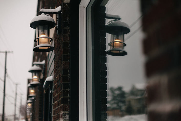 Electric lamps along side building with reflections in window.