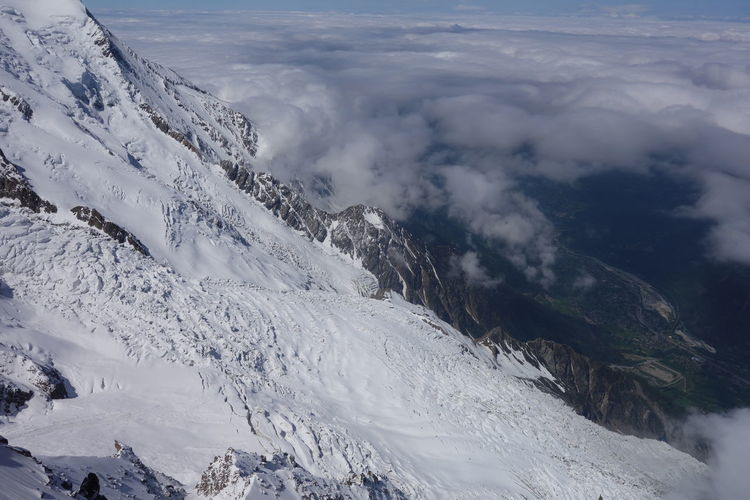 Aerial view of snowcapped mountain against cloudy sky