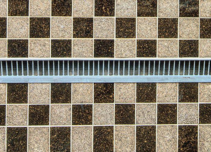 Directly below shot of gutter amidst pattern footpath