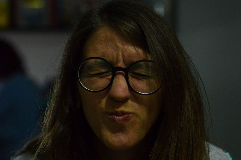 Close-up of woman wearing eyeglasses making face