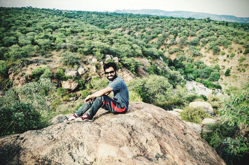 Smiling Mid Adult Man Sitting On Rock Over Landscape