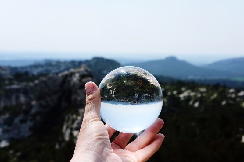 Cropped image of hand holding crystal ball against mountains