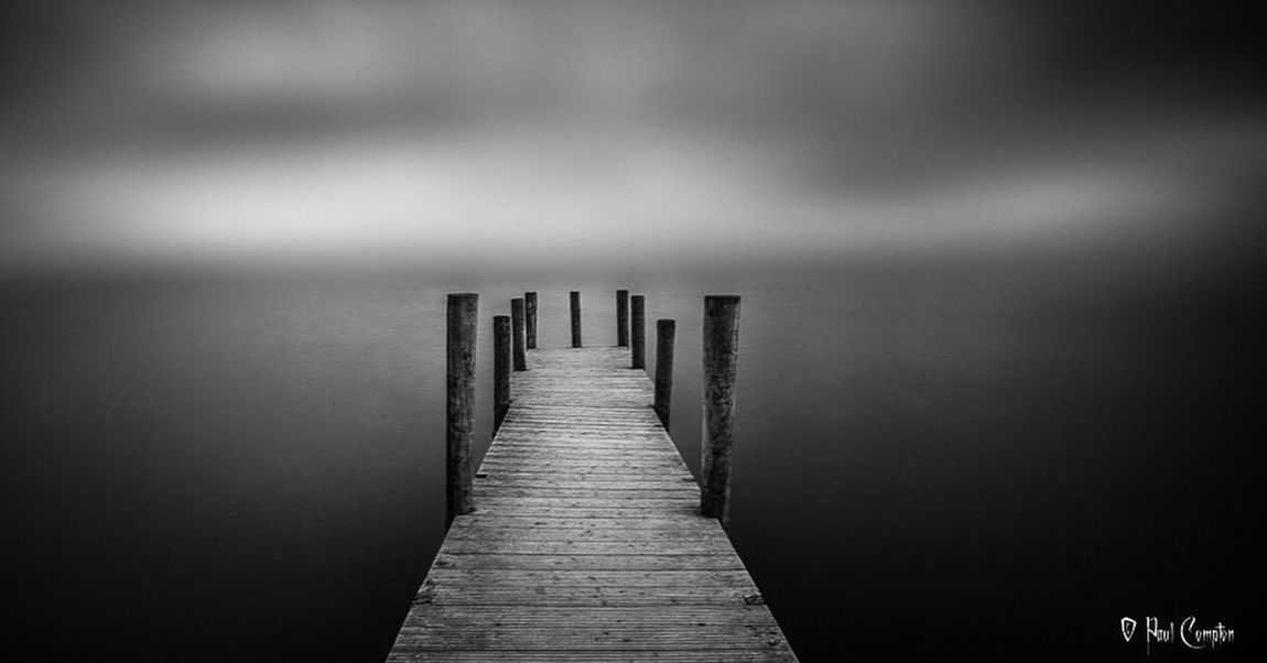 Pier Wooden Post Jetty Lake Tranquility Water Pole Tranquil Scene Calm Wooden Narrow Day The Way Forward Scenics Sea Diminishing Perspective No People Distant Long Non-urban Scene Lake View Lakes  Mono Atmospheric Mood Monochrome
