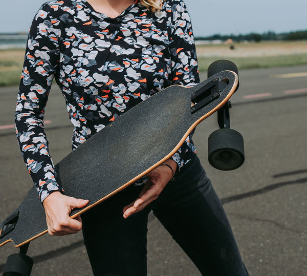 Midsection of woman holding skateboard
