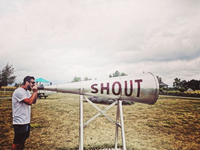 Man shouting on megaphone while standing on land