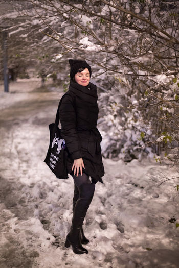 Full length of woman standing on snowcovered land