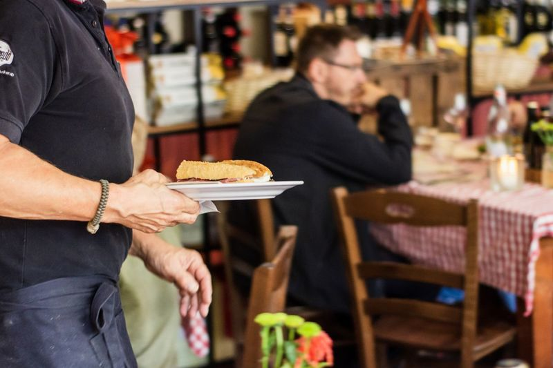 Midsection of waiter holding food while standing in restaurant