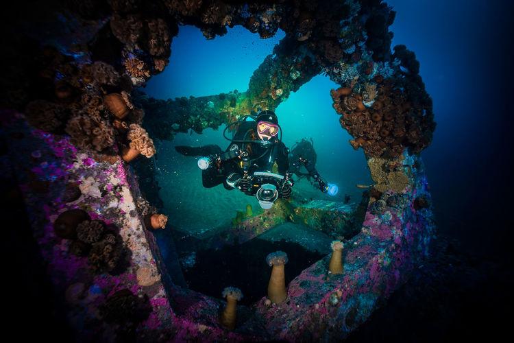 Scuba Divers Filming Concrete Cube Underwater