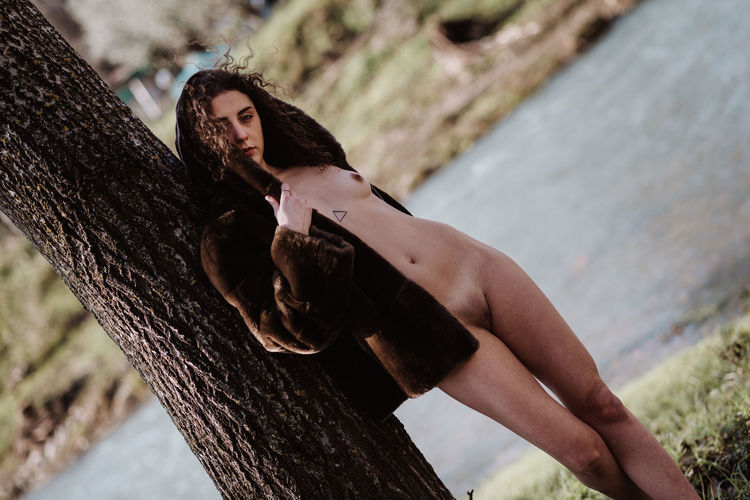 Full length of naked woman standing by tree