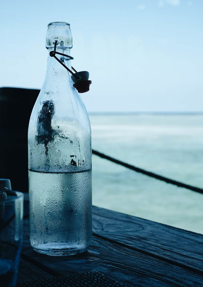 Water Bottle Container Sea Glass - Material Food And Drink Sky Transparent Table Nature Drink Focus On Foreground No People Horizon Close-up Day Refreshment Horizon Over Water Still Life Outdoors Glass