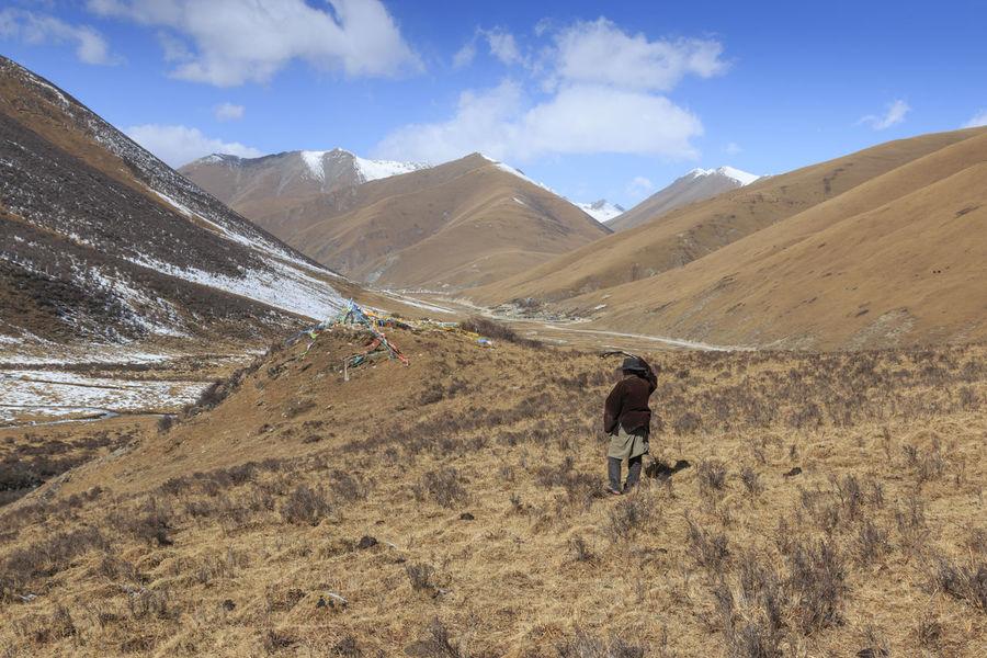 YuShu, China - November 6, 2017: Tibetan shepherd in SiChuan using a slingshot to gather its yaks ASIA Nature Qinghai Sichuan Yushu Beauty In Nature Bird China Cloud - Sky Day Landscape Mountain Mountain Range Nature Outdoors Scenics Shepherd Sky Slingshot Wildlife