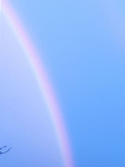 Low angle view of rainbow against clear blue sky