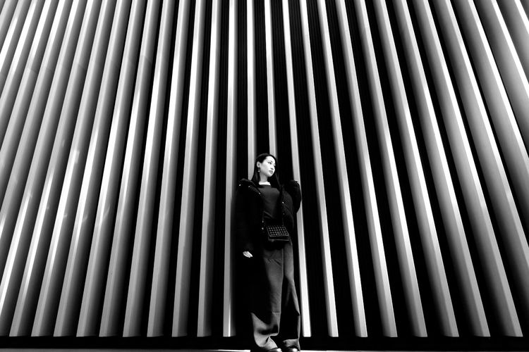 Portrait of woman standing on metallic structure