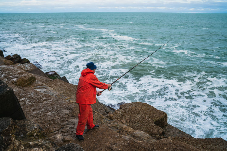 Man fishing on rock by sea